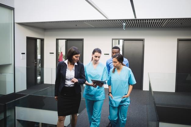 Lekarz i pielęgniarki rozmawiają na cyfrowym tablecie