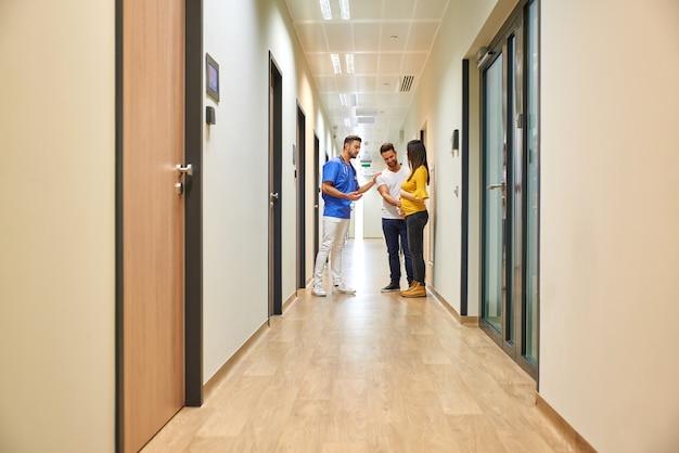 Lekarz i przyszli rodzice na korytarzu