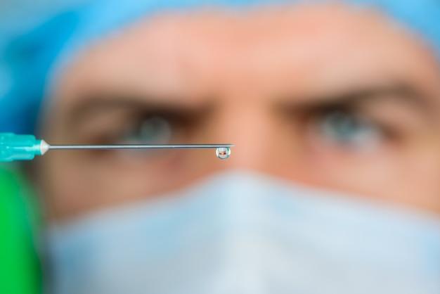 Lekarz iniekcyjny ze strzykawką przygotowuje się do wstrzyknięcia selektywne skupienie profesjonalnego lekarza z