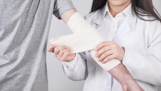 Lekarz kaukaski zakładanie bandaża na rękę pacjenta.