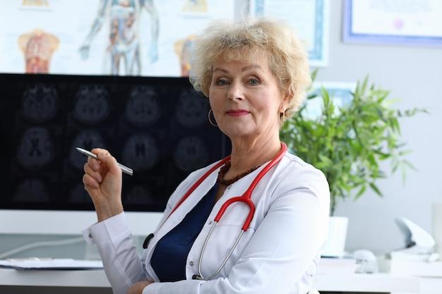 Lekarz kobieta siedzi w biurze trzymając pióro w dłoniach i uśmiecha się.