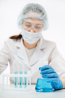 Lekarz kobieta w masce wykonująca test na koronawirusa w laboratorium skupia się na dłoni z kolbą erlenmeyera