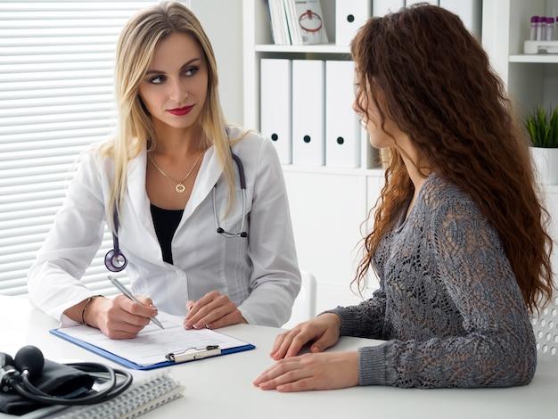 Lekarz konsultuje się z pacjentką. pacjent siedzi w gabinecie lekarskim. diagnostyka, profilaktyka chorób kobiet, opieka zdrowotna, usługi medyczne, konsultacje lub edukacja, koncepcja zdrowego stylu życia