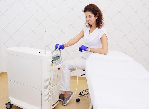 Lekarz kosmetolog na powierzchni lasera neodymowego do zabiegów kosmetycznych i dermatologicznych w nowoczesnej klinice lub salonie kosmetycznym.