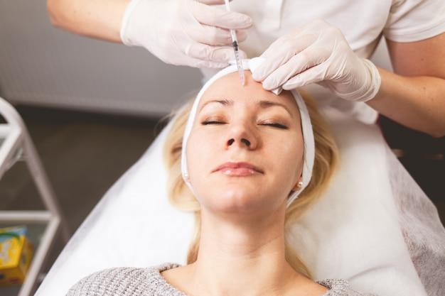 Lekarz kosmetolog wstrzykuje botox w czoło pacjenta