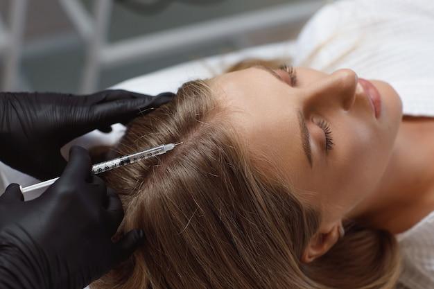 Lekarz kosmetolog wykonujący zastrzyki mezoterapii w głowę kobiety dla mocniejszych i zdrowszych włosów.