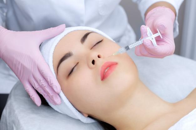Lekarz kosmetolog wykonuje odmładzające zastrzyki na twarz
