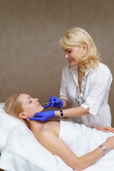 Lekarz kosmetolog wykonuje zabieg odmładzające zastrzyki na twarz w celu ujędrnienia i wygładzenia zmarszczek na skórze twarzy dorosłej kobiety w gabinecie kosmetycznym