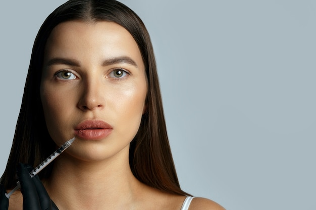 Lekarz kosmetolog wykonuje zabieg powiększania ust młodej, czarującej kobiecie. pusta przestrzeń