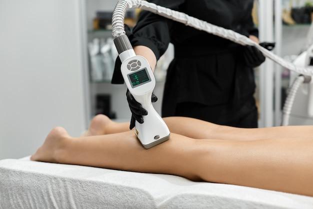 Lekarz kosmetyczny za pomocą masażera endosfery na nogi kobiety w klinice spa w czarnych rękawiczkach