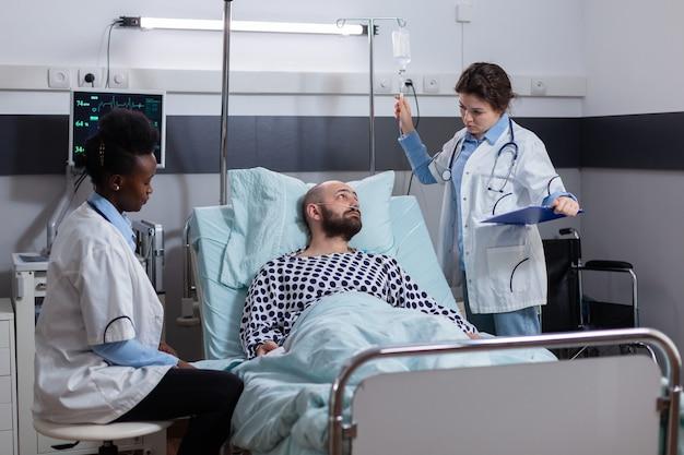 Lekarz lekarz badający objawy choroby pisząc leczenie medyczne w schowku na oddziale szpitalnym...