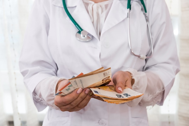 Lekarz liczy banknoty euro, łapówka w medycynie