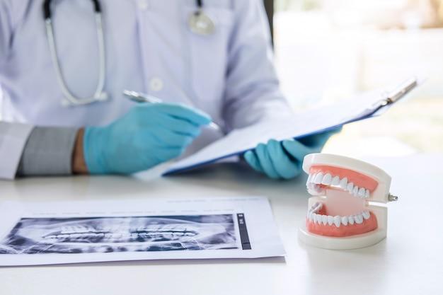 Lekarz lub dentysta pracuje z raportu i filmu rentgenowskiego zębów pacjenta, model i sprzęt stosowany w leczeniu i analizie choroby zębów stomatologicznych