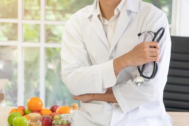 Lekarz lub dietetyk siedzący na biurku z butelką owoców i witamin w klinice.