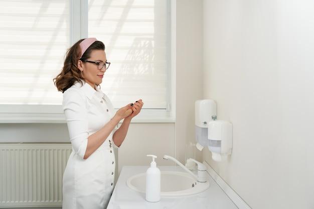 Lekarz lub farmaceuta mycie i dezynfekcja rąk środkiem dezynfekującym
