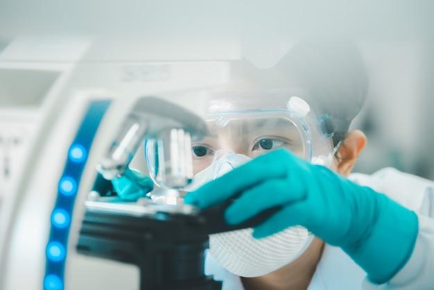 Lekarz lub naukowiec patrząc przez mikroskop w laboratorium badań medycznych lub laboratorium naukowym.
