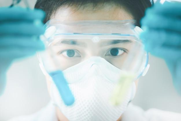 Lekarz lub naukowiec trzymając płynne szczepionki w probówce w laboratorium badań medycznych lub laboratorium naukowym