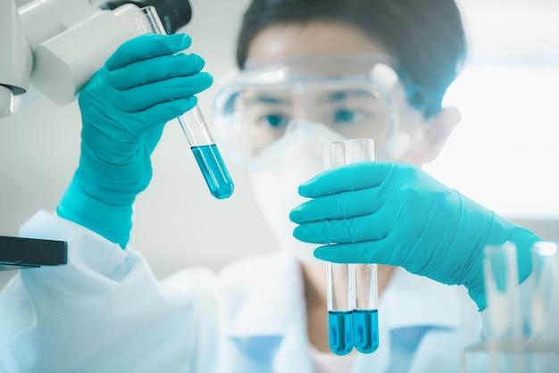 Lekarz lub naukowiec w laboratorium posiadającym płynne szczepionki w laboratorium badawczym lub laboratorium naukowym