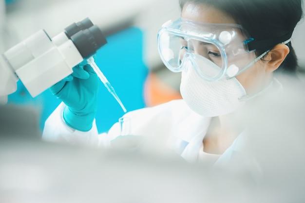 Lekarz lub naukowiec za pomocą pipety upuszczający próbkę do probówki w laboratorium medycznym lub naukowym