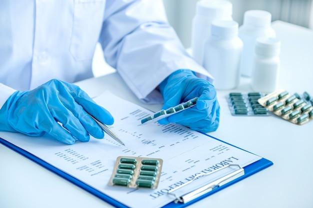 Lekarz lub pielęgniarka ręcznie napisać receptę i trzymając pigułkę leku w biurze apteki, opieki zdrowotnej i koncepcji badania lekarskiego.