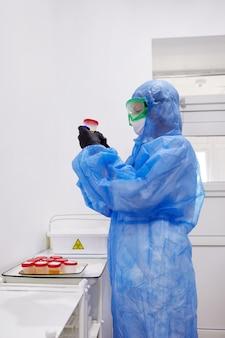 Lekarz lub technik szuka próbki moczu w butelce przygotowanej do badania moczu pod mikroskopem