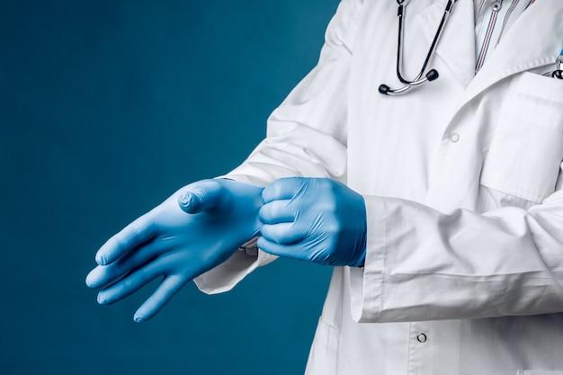 Lekarz ma na rękach niebieskie rękawiczki medyczne.