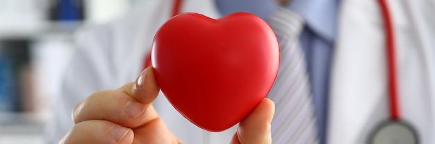 Lekarz medycyny mężczyzna trzymając się za ręce i obejmujące czerwone serce zabawki