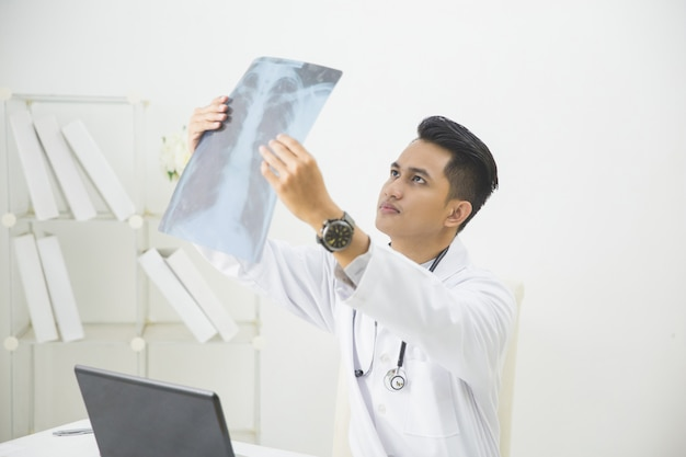 Lekarz medycyny patrzeje promieniowanie rentgenowskie wizerunek w biurze