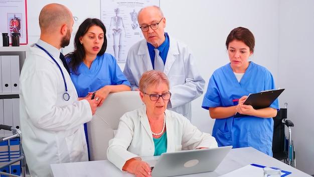 Lekarz medycyny pracujący na laptopie podczas odprawy ze współpracownikami i pielęgniarką robienia notatek. ekspert kliniczny terapeuta rozmawiający z kolegami o chorobie, specjalista od medycyny