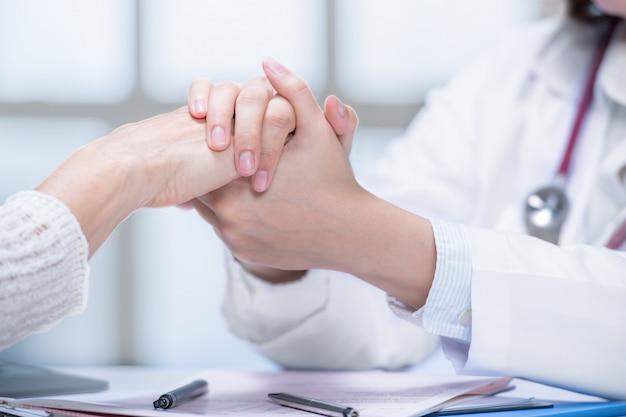 Lekarz medycyny uspokaja pacjenta, trzymając ręce w szpitalnym otoczeniu