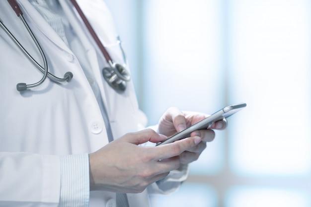 Lekarz medycyny używa mądrze telefon dla pracy w szpitalu