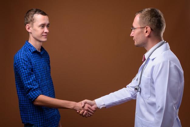 Lekarz mężczyzna i pacjent młody człowiek na brązowym