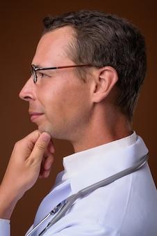 Lekarz mężczyzna przed brązową ścianą