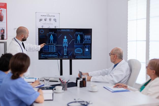 Lekarz mężczyzna przedstawiający radiografię mózgu analizującą wiedzę medyczną pracujący w sali konferencyjnej