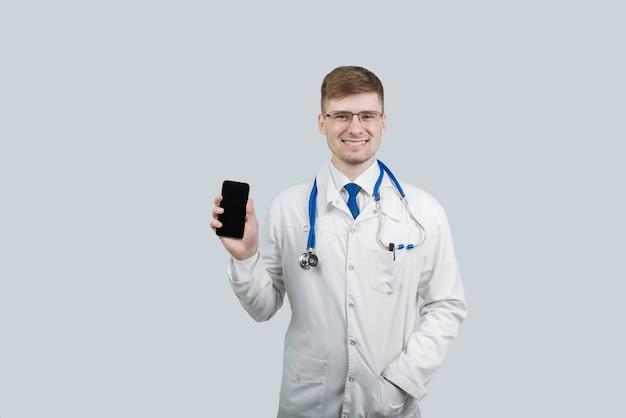 Lekarz mężczyzna trzyma tephon w ręku i uśmiecha się