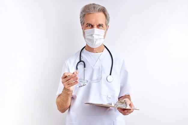 Lekarz mężczyzna ubrany w okulary ochronne do przygotowania do pracy, starszy mężczyzna w białym garniturze medycznym patrzy na aparat na białym tle na białej przestrzeni