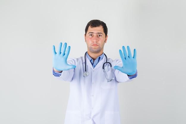 Lekarz mężczyzna w białym fartuchu, pokazując ręce z rękawiczkami medycznymi i patrząc uważnie