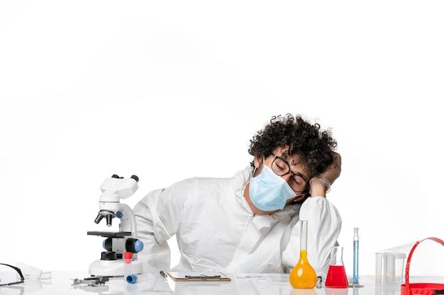 Lekarz mężczyzna w kombinezonie ochronnym i masce pracuje i czuje się zmęczony na białym
