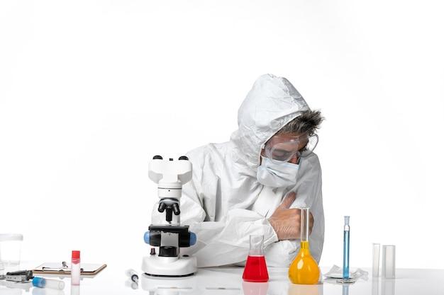 Lekarz mężczyzna w kombinezonie ochronnym i masce siedzi i czuje się zmęczony na jasnym białym