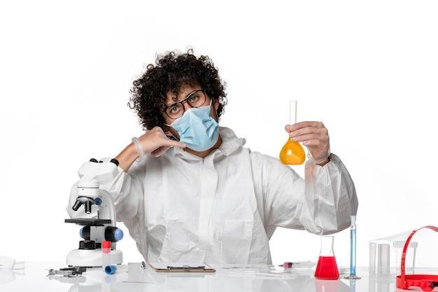 Lekarz mężczyzna w kombinezonie ochronnym i masce trzymającej kolbę z żółtym roztworem na białym