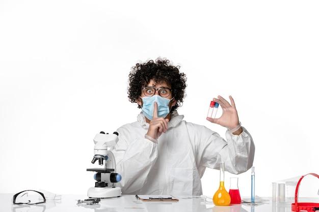 Lekarz mężczyzna w kombinezonie ochronnym i masce trzymającej kolby na białym