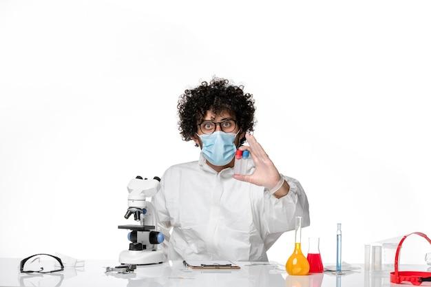 Lekarz mężczyzna w kombinezonie ochronnym i masce trzymającej kolby na jasnym białym tle