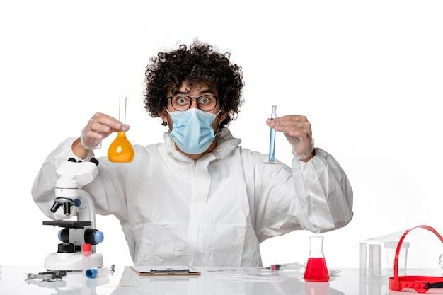 Lekarz mężczyzna w kombinezonie ochronnym i masce trzymającej kolby z roztworami na białym
