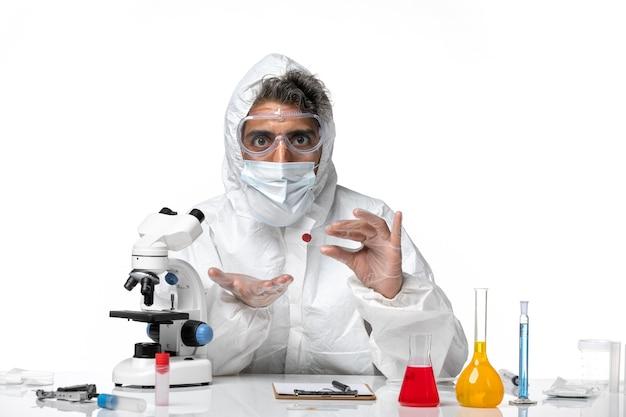 Lekarz mężczyzna w kombinezonie ochronnym i sterylną maską trzymającą kolbę na jasnym białym tle