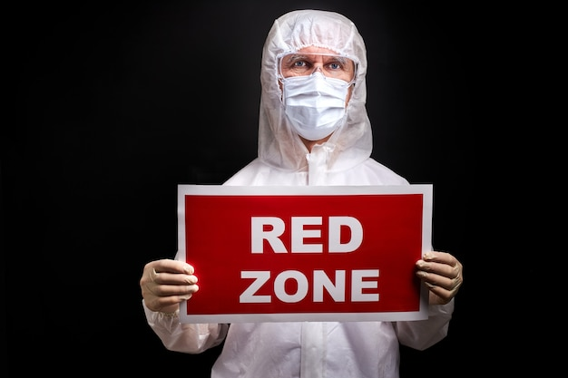 Lekarz mężczyzna w ochronnym kombinezonie medycznym, trzymając tablet z napisem czerwonej strefy