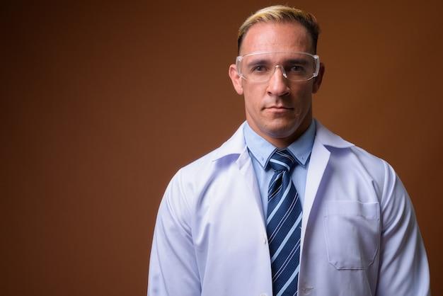 Lekarz mężczyzna w okularach ochronnych na brązowym