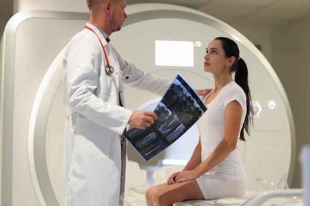 Lekarz mężczyzna wyjaśniający pacjentce wynik badania rezonansu magnetycznego w diagnostyce klinicznej i