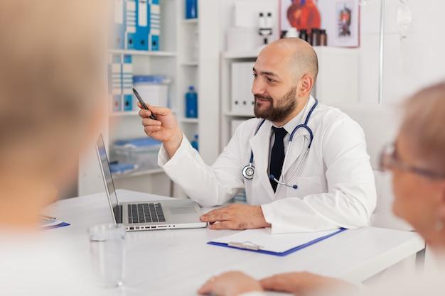 Lekarz mężczyzna wyjaśniający wiedzę medyczną dotyczącą choroby zespołowi szpitalnemu omawiający leczenie farmakologiczne pigułek pracujących w sali konferencyjnej naukowej