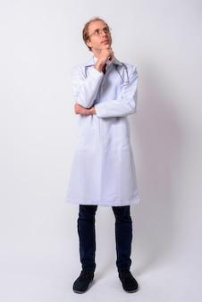 Lekarz mężczyzna z blond włosami w okularach na białej ścianie