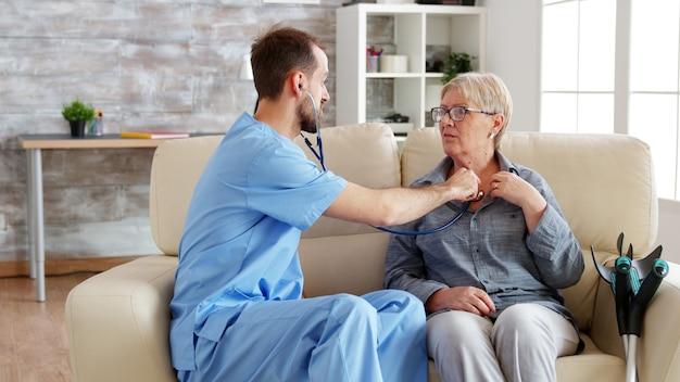 Lekarz mężczyzna zakładający stetoskop i słuchający bicia serca staruszki w domu opieki